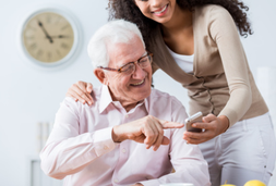 Senior mit Enkelin und Handy